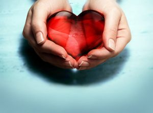 Holding red glass heart in hands
